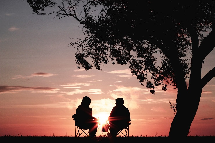 Two people sitting underthe tree infront of sunset